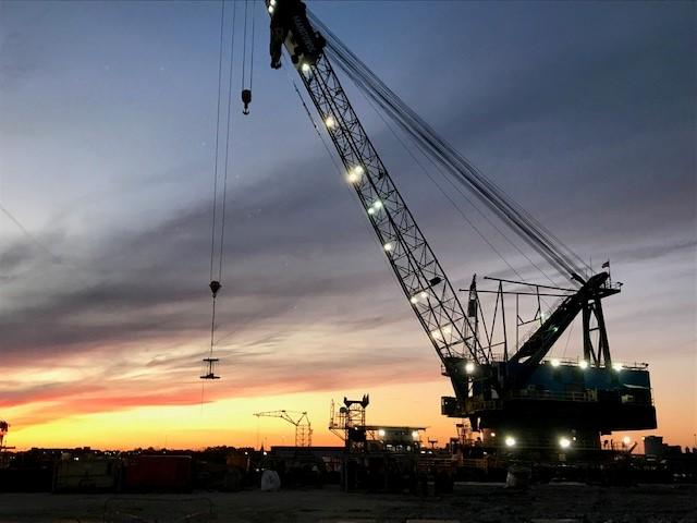 Alabama Shipyard Arapaho derrick barge operating an 800-ton crane as the sun is setting